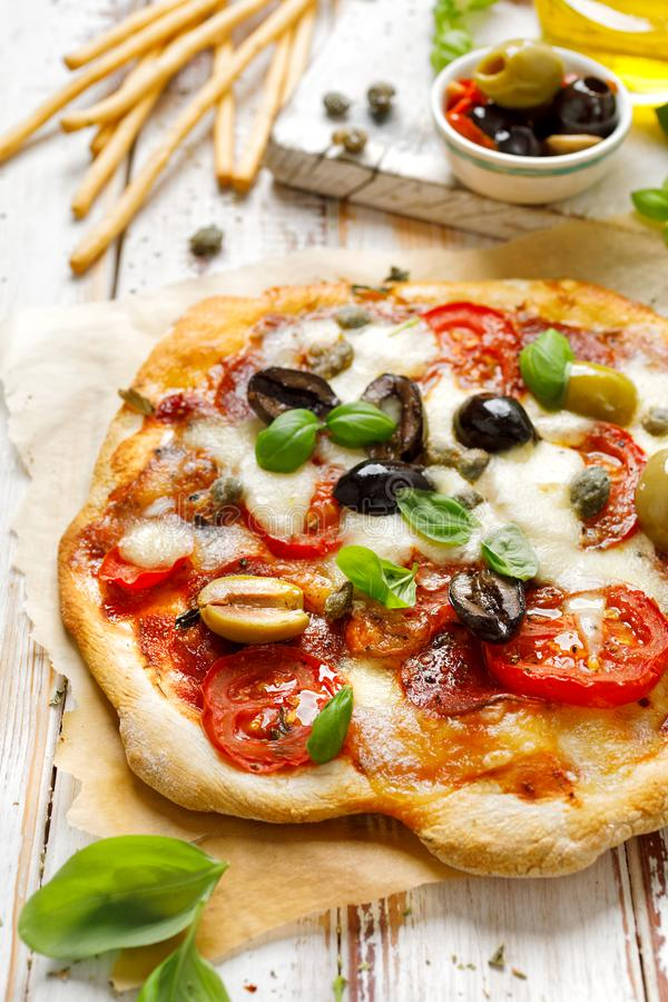 Pizza caseiro com tomates, azeitonas, salame, mozzarella e manjericão fresca em uma tabela rústica de madeira fotografia de stock royalty free