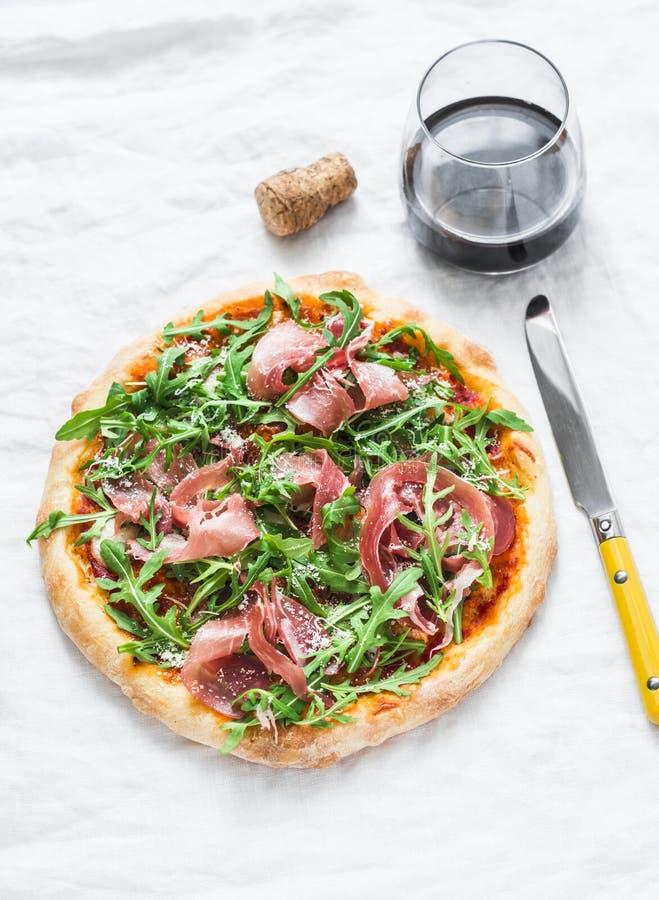 Pizza caseiro da rúcula do Prosciutto e um vidro do vinho tinto no fundo claro, vista superior Aperitivos deliciosos imagens de stock