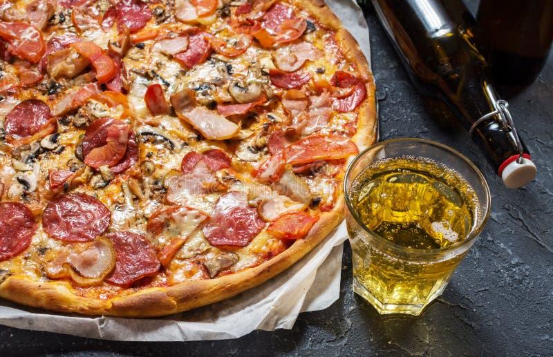 Pizza caseiro fresca com pepperoni, presunto, queijo e vidro da cerveja no fundo de pedra rústico foto de stock royalty free
