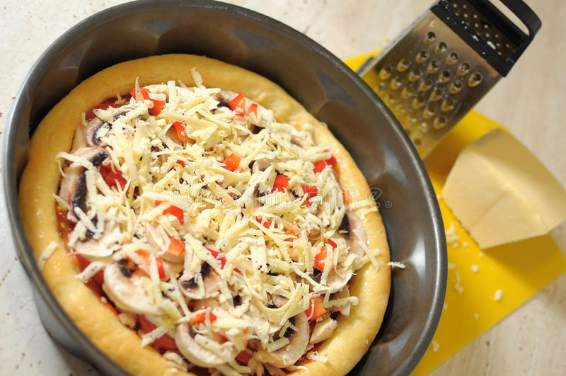Pizza caseiro, ralador e queijo, processo de cozimento Camada de queijo raspado fotografia de stock