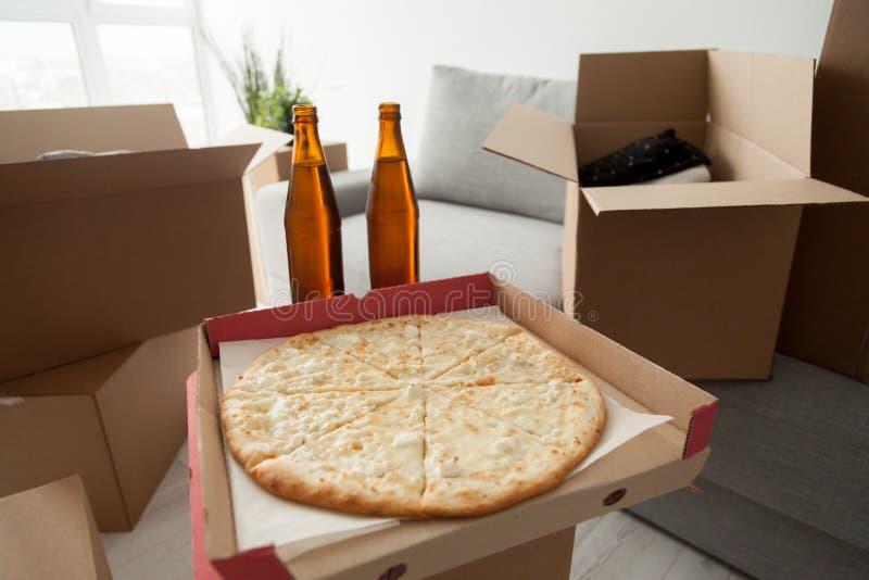 Pizza, cerveja e caixas, movendo-se no partido da festa de inauguração da celebração imagem de stock