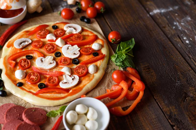 Pizza with champignons, cherry tomatoes, bell peppers, salami, mozzarella and olives before baking with space for text royalty free stock photos