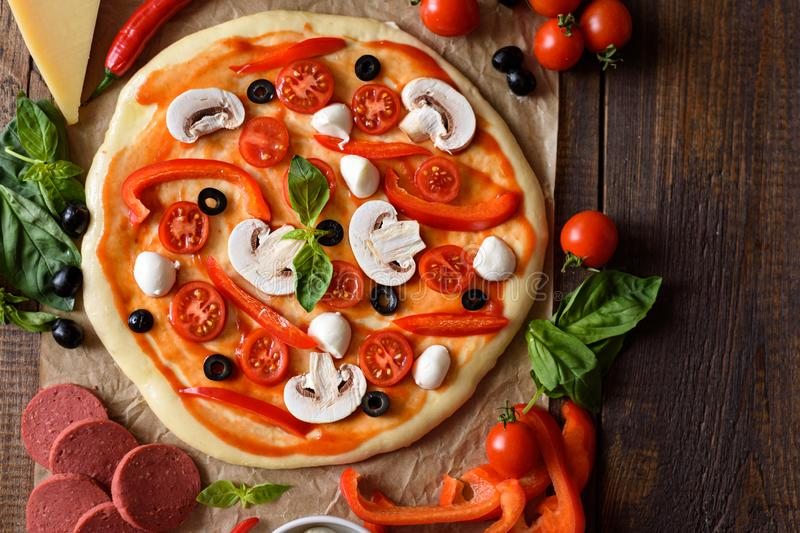 Pizza with champignons, cherry tomatoes, bell peppers, salami, mozzarella and olives before baking with space for text royalty free stock photo