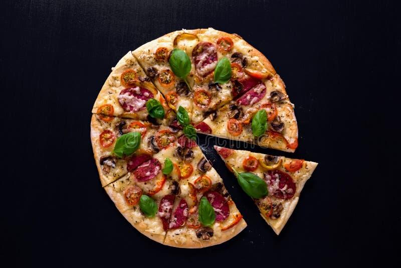 Pizza chaude et délicieuse avec des tomates fromage et champignons de salami tout préparés sur un fond en bois noir Vue supérieur image libre de droits
