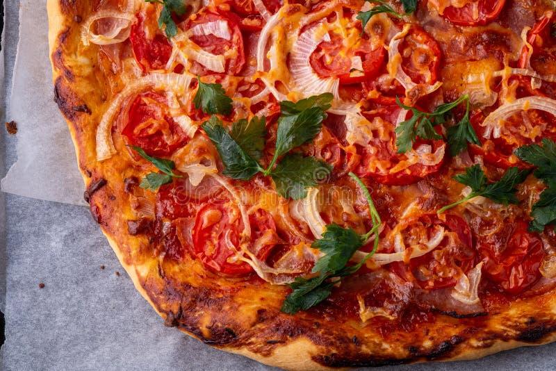 Pizza chaude fraîchement cuite avec le persil d'oignon de tomate de viande de jambon de fromage fait maison sur le papier parchem photos libres de droits