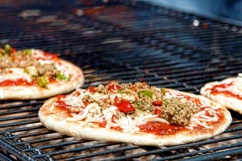 Pizza che cucina sulla griglia del carbone di legna immagine stock libera da diritti