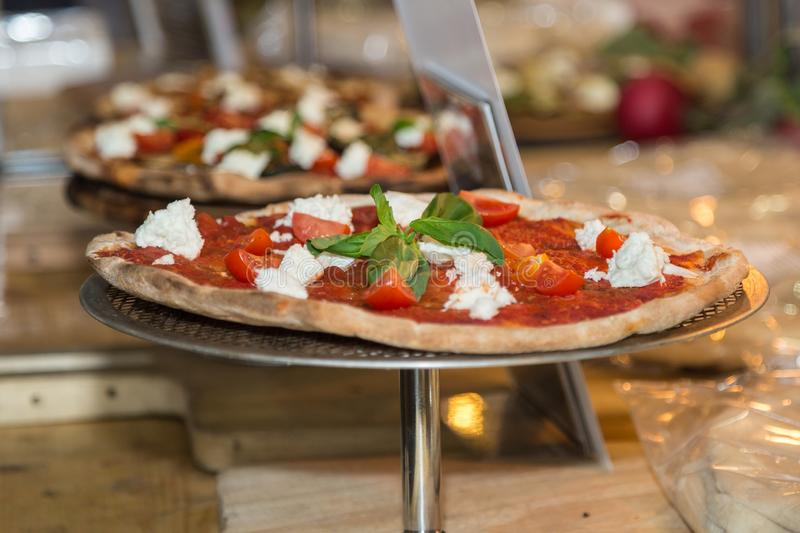 Pizza with Cheese, Cherry Tomatoes and Basil on a Round Metal Display Case royalty free stock images