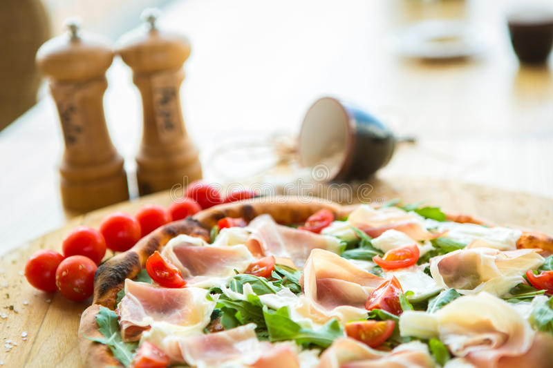 Pizza with cherry tomatoes, prosciutto and ruccola. On wooden table royalty free stock image