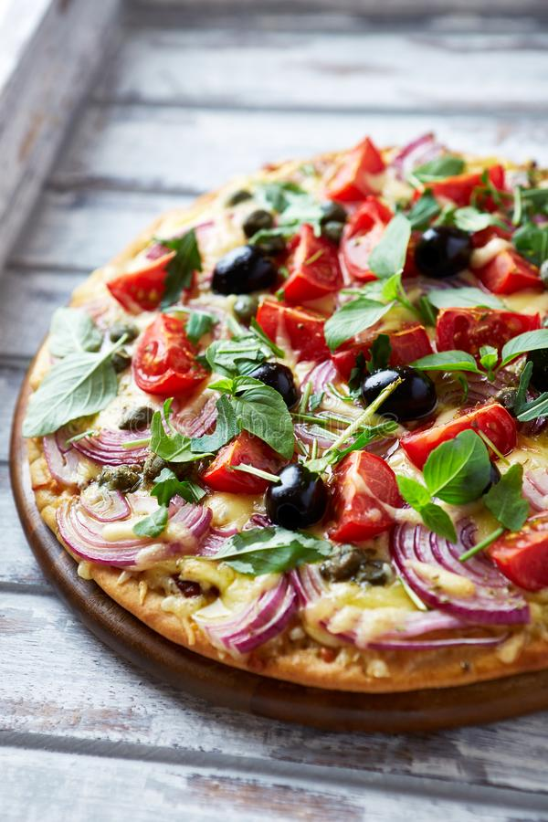 Pizza with cherry tomatoes, red onion and capers topped with arugula and basil. Italian food royalty free stock photo