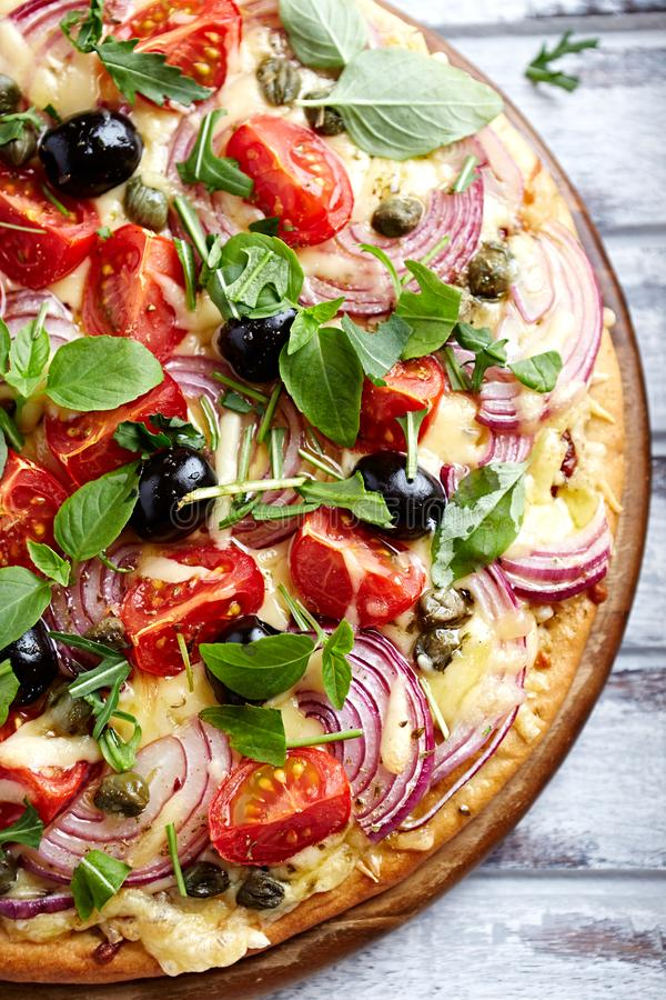 Pizza with cherry tomatoes, red onion and capers topped with arugula and basil. Italian food. Top view stock image