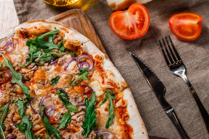 Pizza with chicken, arugula, cheese and onions on wooden rustic table. royalty free stock photo