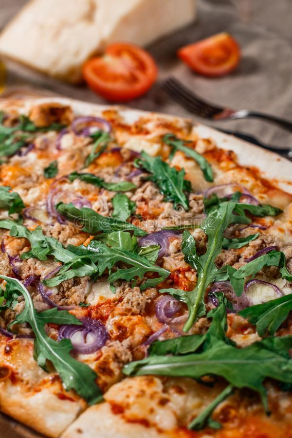 Pizza with chicken, arugula, cheese and onions on wooden rustic table. stock image