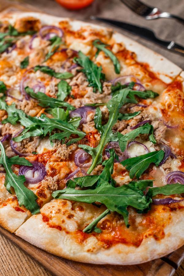 Pizza with chicken, arugula, cheese and onions on wooden rustic table. stock photography