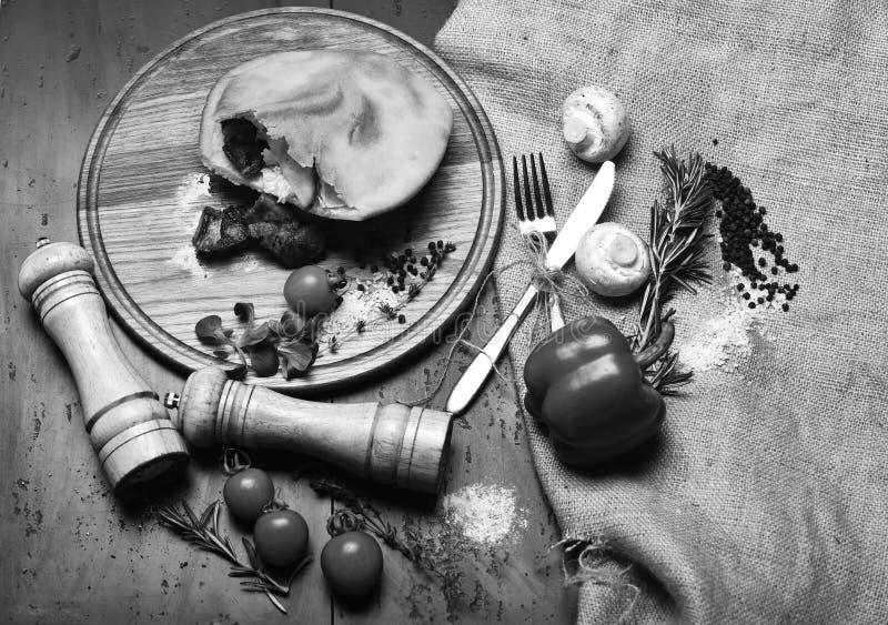 Pizza chiusa con il materiale da otturazione della carne, fondo grigio Cucina rustica fotografia stock