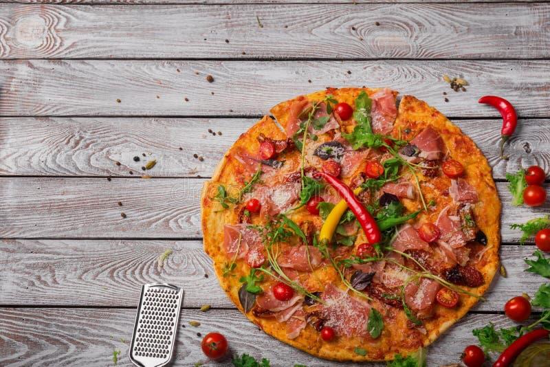Pizza clássica com pimenta de pimentão, verdes, carne Pizza em um fundo marrom Restaurante italiano luxuoso Copie o espaço foto de stock