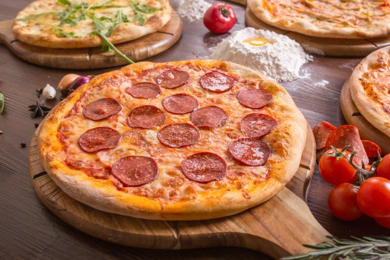 Pizza clasificada con los salchichones, carne, margarita en un soporte de madera imagen de archivo