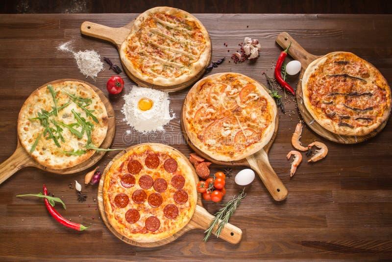 Pizza classificada com marisco e queijo, quatro queijos, pepperoni, carne, margarita em um suporte de madeira com especiarias foto de stock