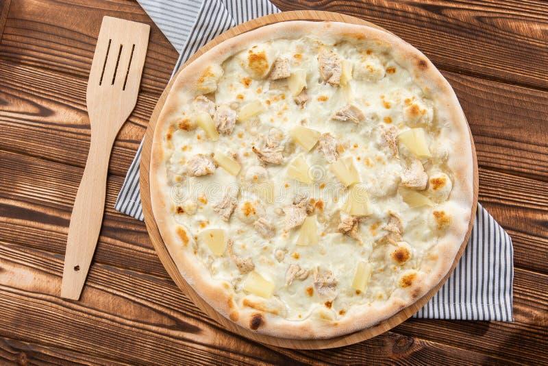 A pizza cobriu com saque do molho, da galinha, do queijo e do abacaxi na placa de madeira na tabela de madeira Foto da pizza hava fotografia de stock