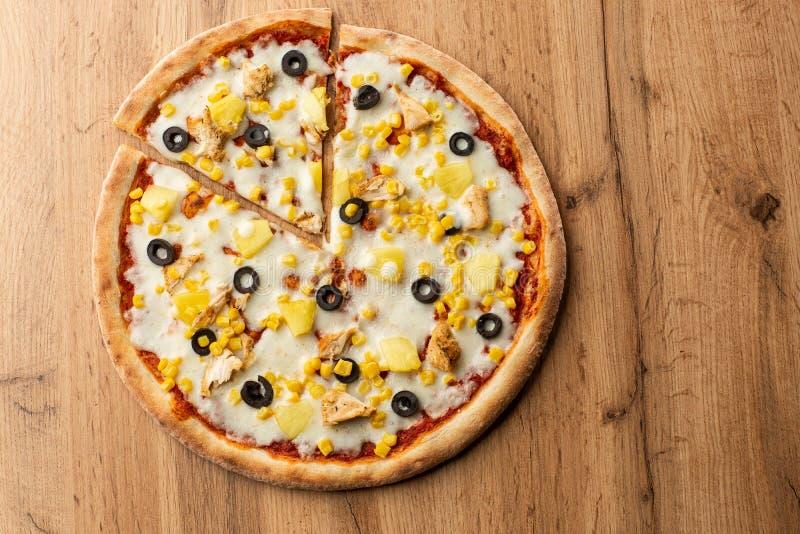 A pizza cobriu com saque do molho, da galinha, do queijo e do abacaxi na placa de madeira na tabela de madeira Foto da pizza hava imagem de stock