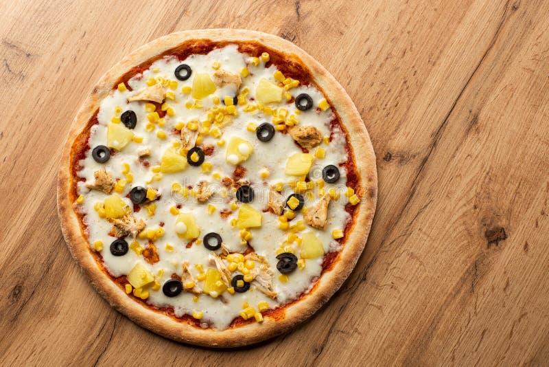 A pizza cobriu com saque do molho, da galinha, do queijo e do abacaxi na placa de madeira na tabela de madeira Foto da pizza hava imagem de stock royalty free