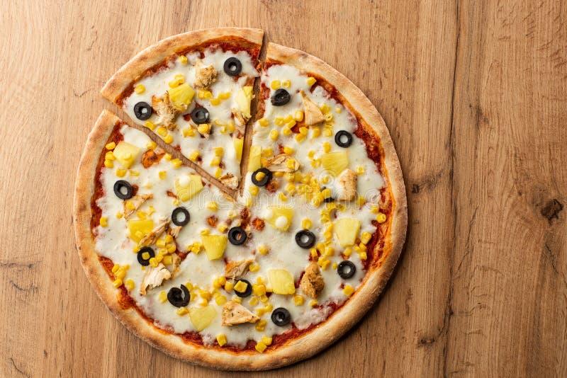 A pizza cobriu com saque do molho, da galinha, do queijo e do abacaxi na placa de madeira na tabela de madeira Foto da pizza hava fotos de stock