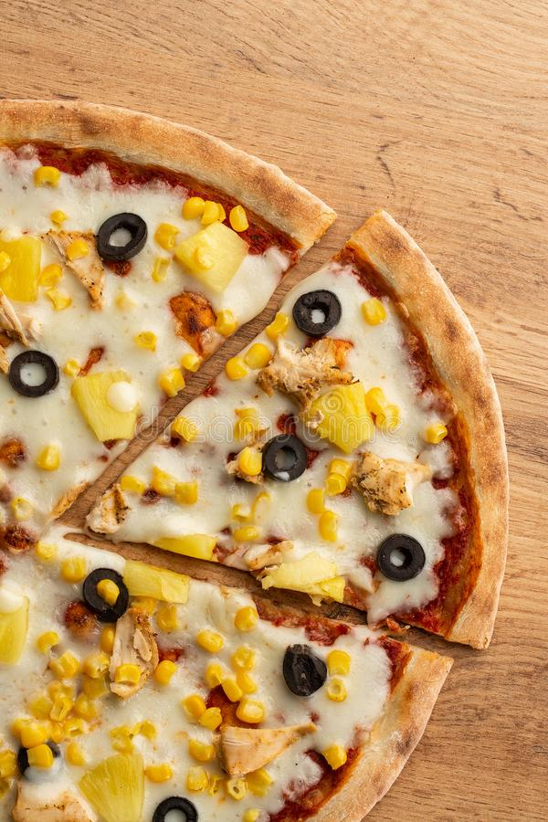 A pizza cobriu com saque do molho, da galinha, do queijo e do abacaxi na placa de madeira na tabela de madeira Foto da pizza hava fotografia de stock royalty free