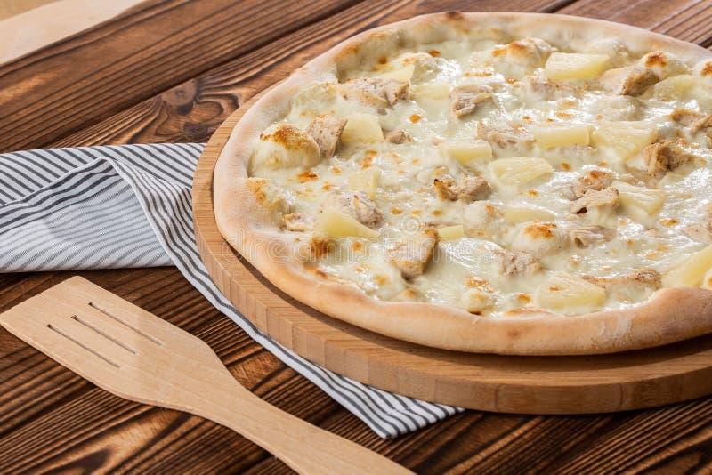 A pizza cobriu com saque do molho, da galinha, do queijo e do abacaxi na placa de madeira na tabela de madeira Foto da pizza hava imagens de stock royalty free