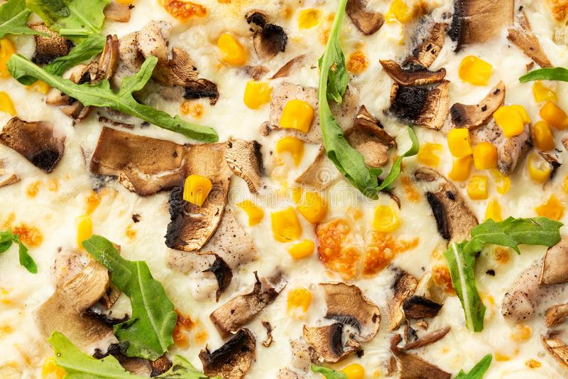 Pizza cocida fresca deliciosa italiana con queso de fusión, las setas cortadas, el arugula y el maíz dulce en rústico texturizada imágenes de archivo libres de regalías