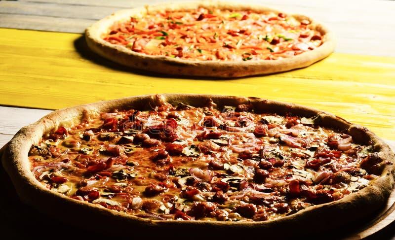 Pizza com bacon, queijo e alcaparras no fundo de madeira amarelo fotos de stock royalty free