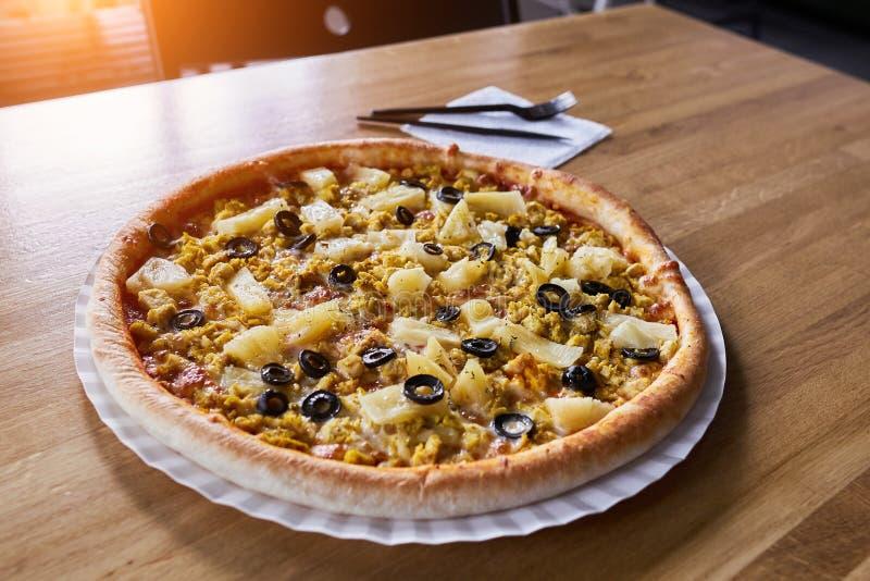 Pizza com galinha e abacaxi na tabela no restaurante fotografia de stock