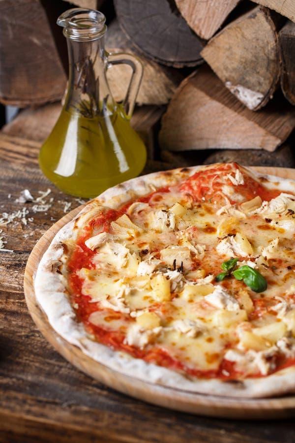 Pizza com galinha e abacaxi no fundo da lenha fotos de stock royalty free