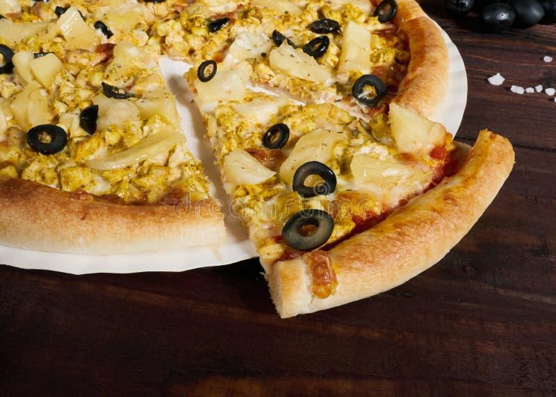 Pizza com galinha e abacaxi com parte cortada na tabela fotos de stock
