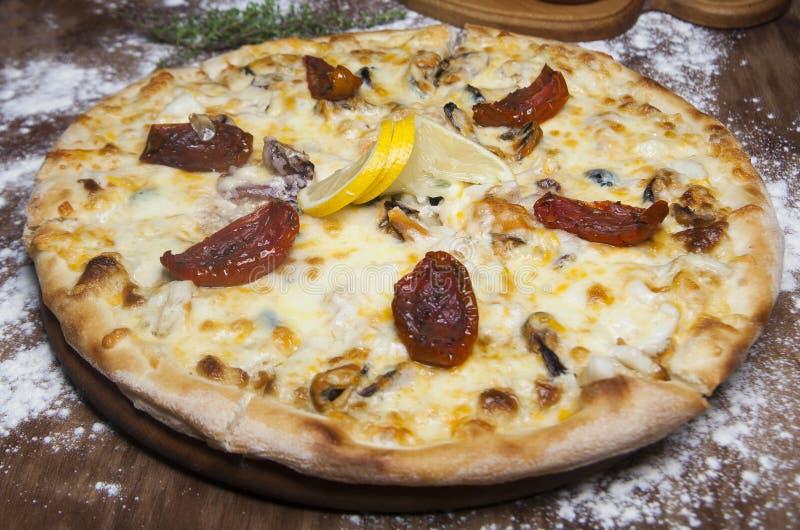 Pizza com marisco, os tomates secados e o queijo imagens de stock