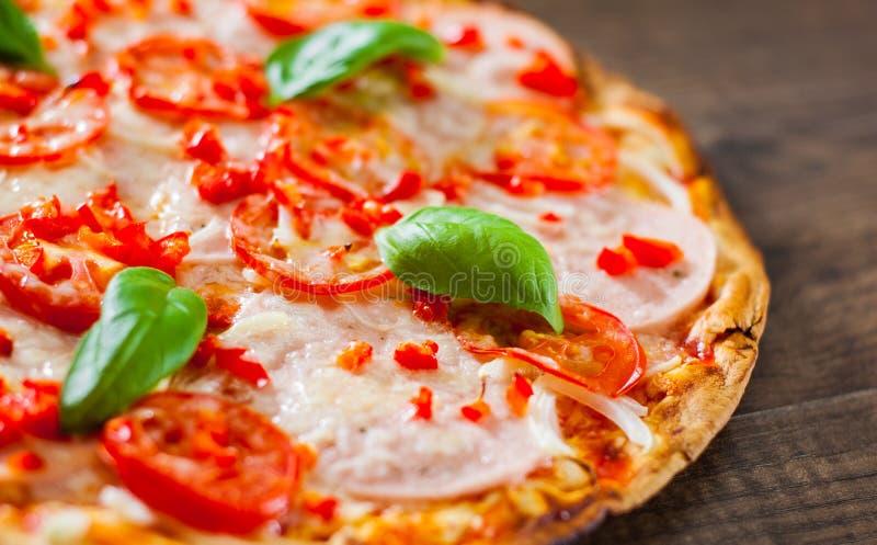 Pizza com mozzarella, presunto, tomates, pimenta, especiarias e manjericão fresca Pizza italiana em de madeira imagens de stock royalty free