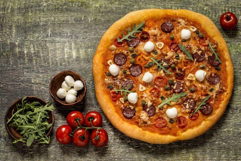 Pizza com mussarela, alcaparras, r?cula e tomates no fundo de madeira fotografia de stock