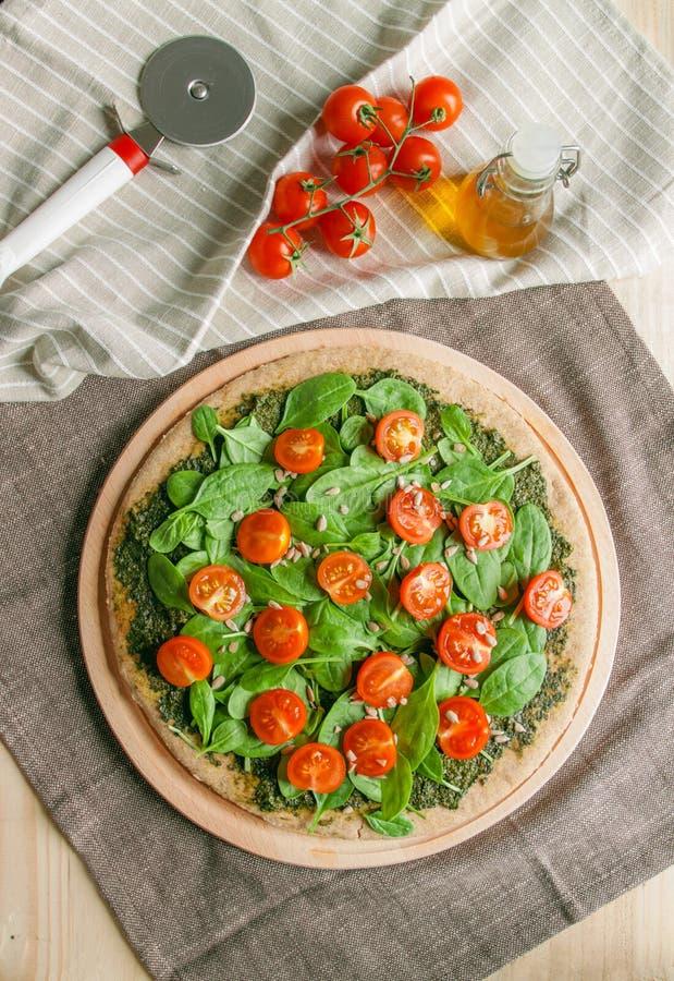 Pizza com os tomates do pesto, dos espinafres e de cereja fotos de stock royalty free