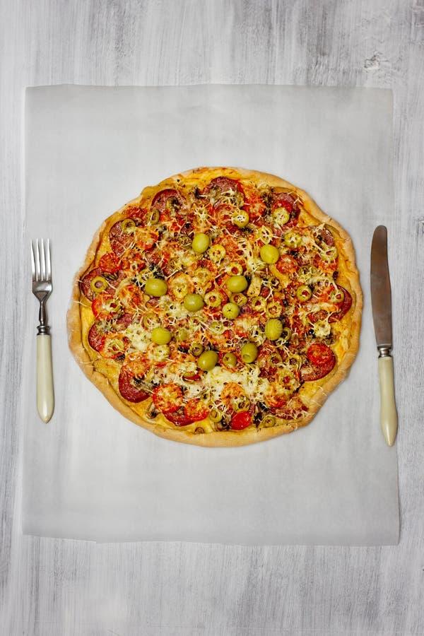 Pizza com os tomates do salami e de cereja fotografia de stock royalty free