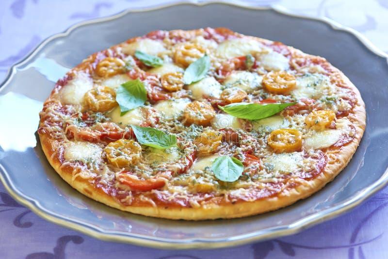 Pizza com pepperoni, tomates, pimenta e mussarela imagem de stock