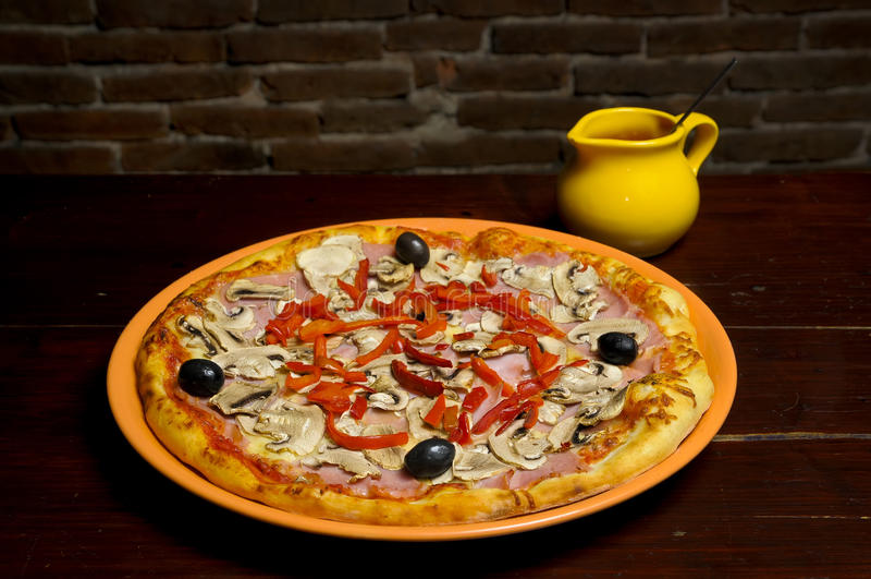 Pizza com presunto, cogumelos, pepperoni e azeitonas imagens de stock royalty free