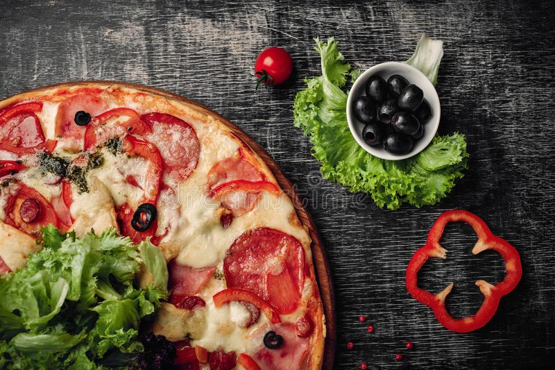 Pizza com presunto, salame, queijo, cogumelos, tomates de cereja, pimentas de sino e salada em uma placa de giz preta fotos de stock