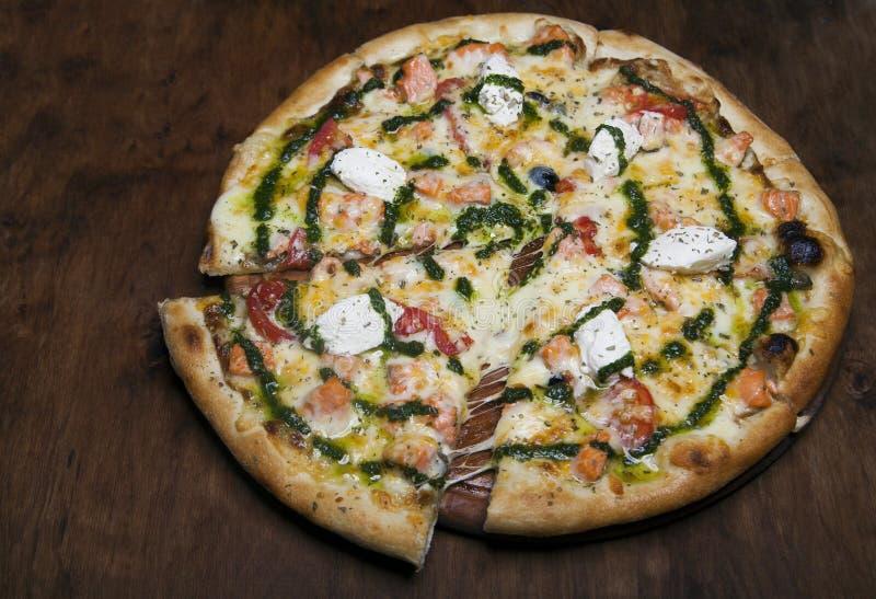 Pizza com queijo e salmões em uma tabela de madeira marrom fotografia de stock