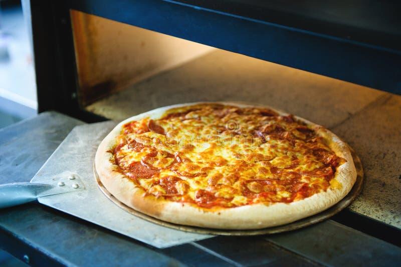 Pizza com queijo em uma bandeja do metal para cozer em um forno bonde foto de stock