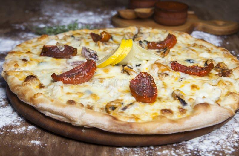 A pizza com queijo sol-secou tomates marisco e limão foto de stock