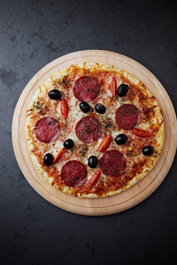 Pizza com salame, mozzarella, tomates de cereja, azeitonas pretas e oréganos A casa fez o alimento Conceito para um saboroso e en fotos de stock royalty free