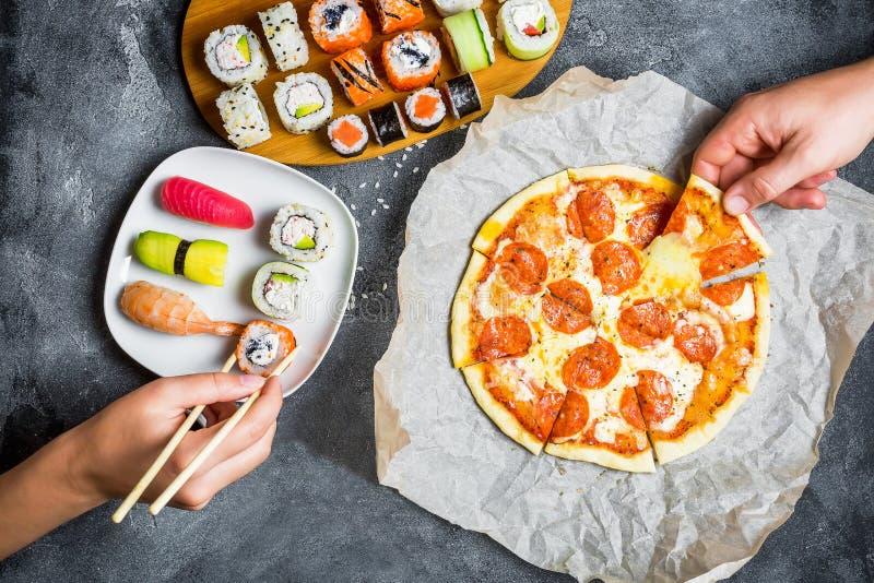 A pizza com salame, o grupo de rolos de sushi e as mãos tomam o alimento Fundo do alimento Configuração lisa, vista superior fotos de stock royalty free