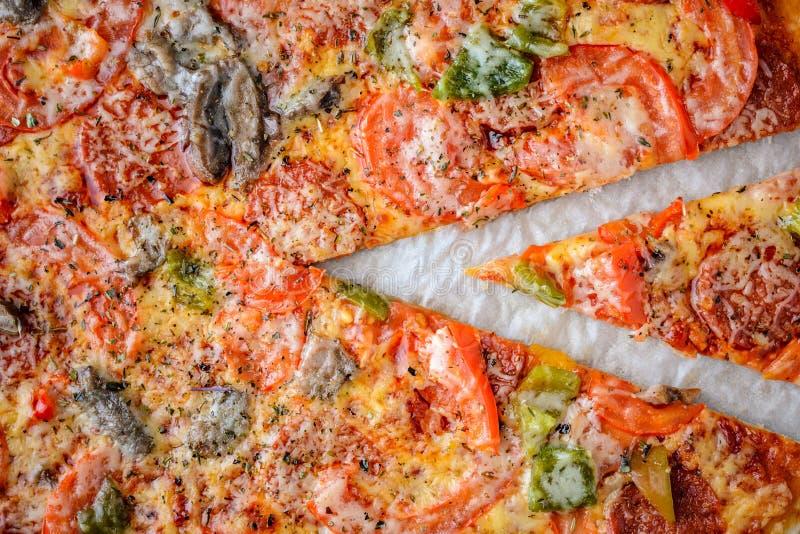 A pizza com salame, tomates, pimenta e cogumelos é a parte superior vie foto de stock royalty free