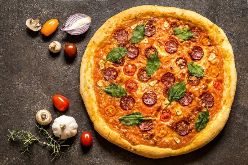 Pizza com salsicha do salame, espinafres e tomates de cereja em um fundo escuro imagem de stock