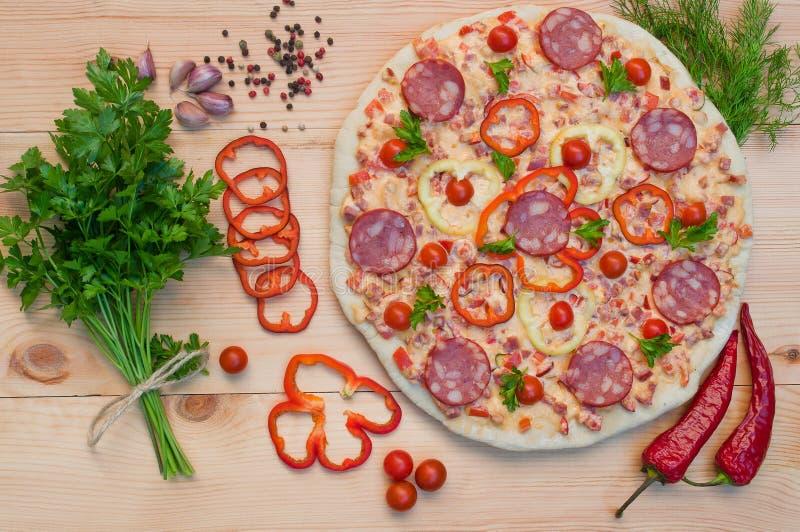 Pizza com salsicha e queijo, tomates de cereja e pimentas na foto de stock royalty free