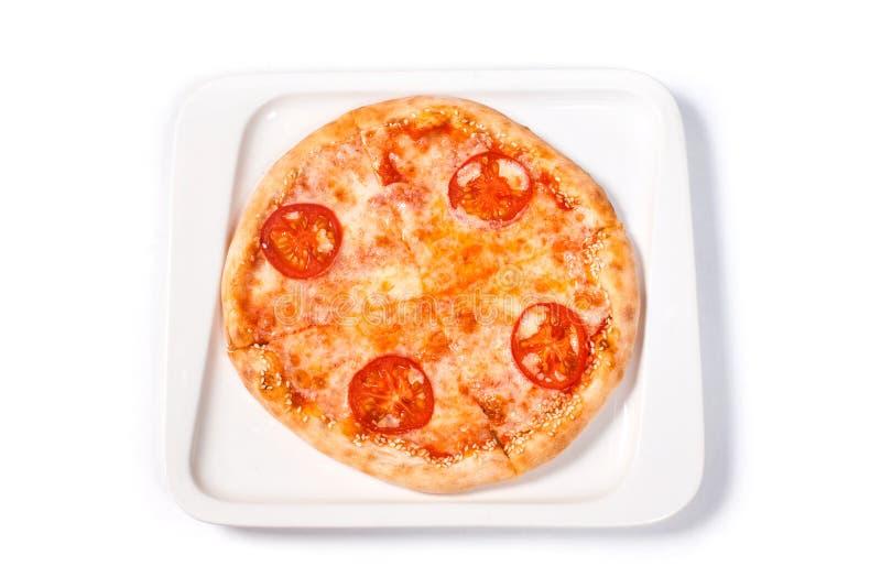 Pizza com tomate e queijo em uma placa branca em um fundo branco isolado foto de stock