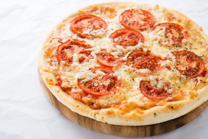 Pizza com tomate, queijo e manjericão seca no fim branco do fundo acima fotografia de stock royalty free